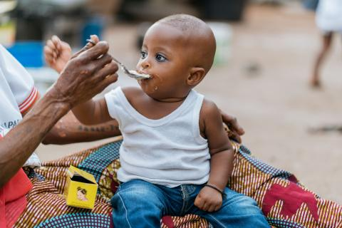 A child being fed with corn-based porridge