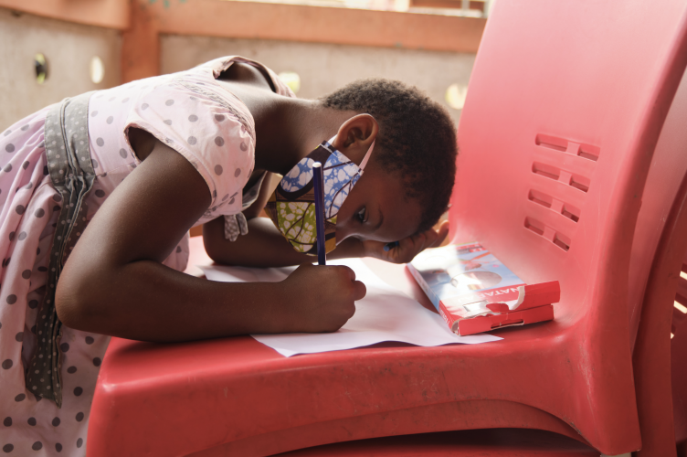 A little girl bends over a chair to draw on a piece of paper