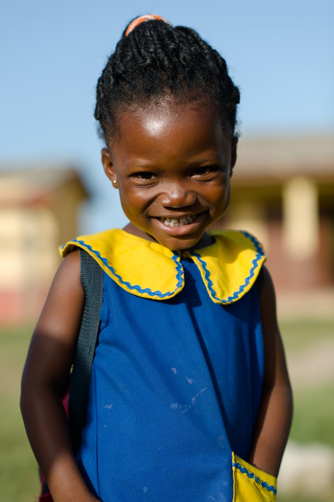 A young girl smiling on her way to school