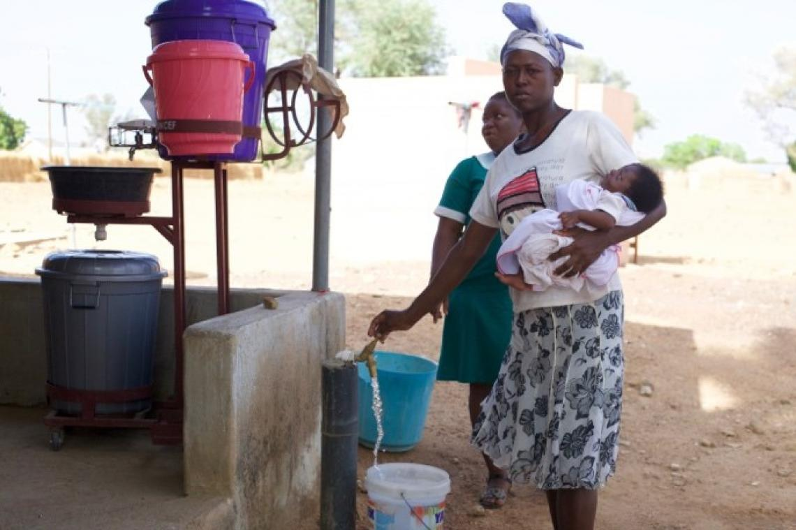 A nursing mother uses a water facility at the Sumbrungu health centre.
