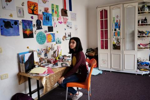 Teen sits at her desk by a wall filled with her drawings at her home.