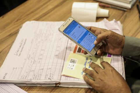 Official using phone to update vaccination records