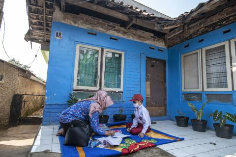 A teacher and her student outside of his house in Indonesia