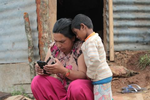 A woman uses her mobile phone while her son watches