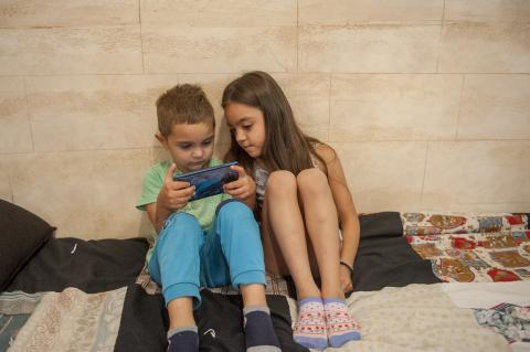 Brother and sister playing a game on their phone