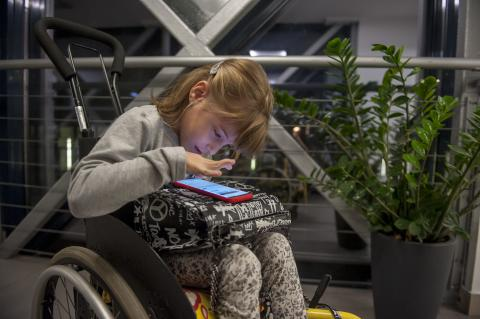 A girl in a wheel chair uses a smartphone