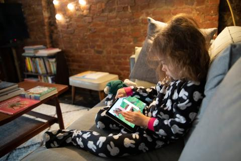 Child practices the alphabet on a tablet at home