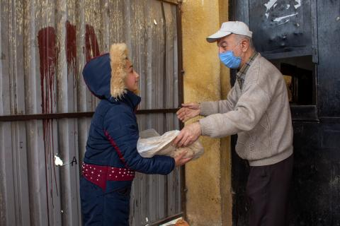 Child distributes food medical information to elderly