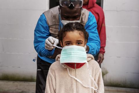 Seven-year-old girl is given a protective mask