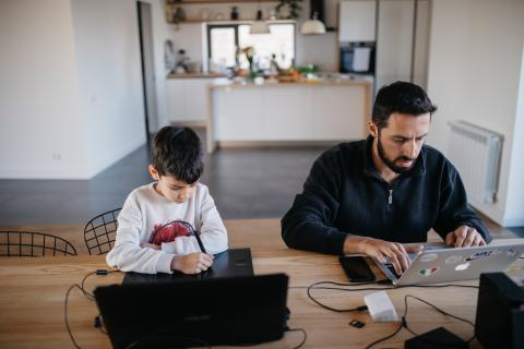 Boy sits at a computer next to his father