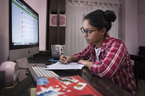 Teenage student is taking an Online Assessment Examination from her home