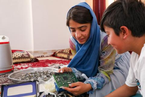 Teen girl shows her younger brother her robot prototype