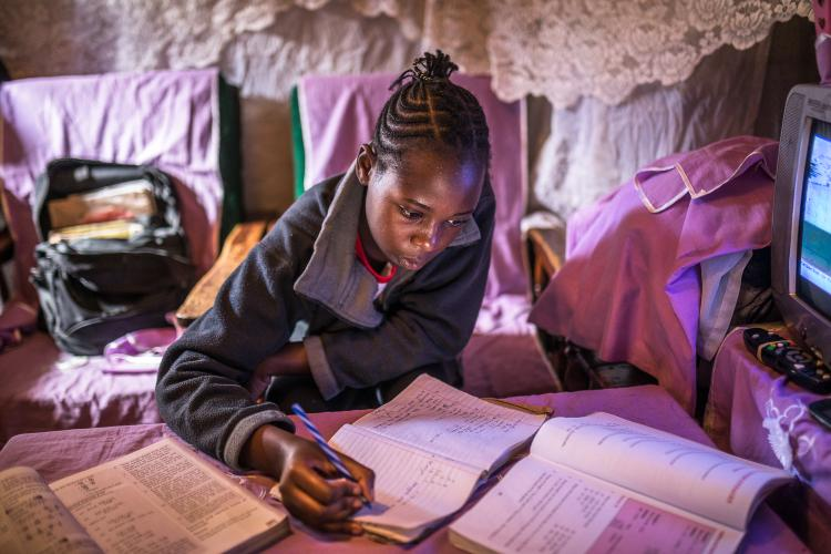 A girl doing school work at home in Kibera, Kenya.