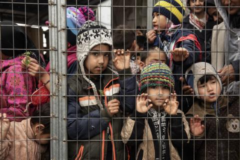 On 8 March 2020, children line up for fruit juice behind a barbwire fence in the Reception and Identification Centre in Moria, on the island of Lesvos, in Greece.