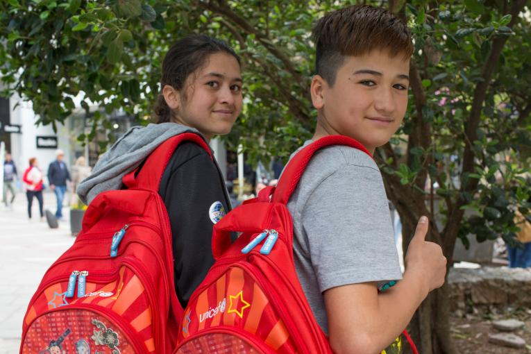 Two Afghani children with red UNICEF schoolbags smile at the camera