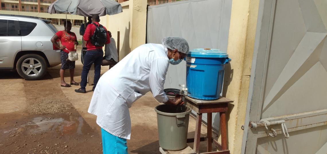 Mme Camara née Djénabou Mali Diallo lavant les mains au niveau du dispositif institué à cet effet à la rentrée de l'INSE.