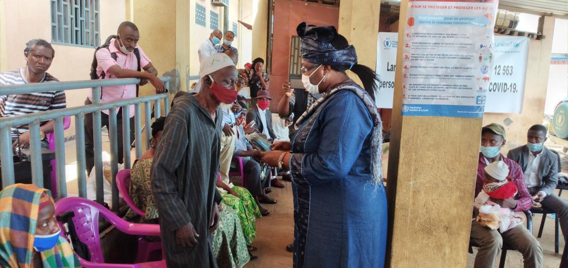 Hadja Mariama Sylla, Ministre de l'Action sociale et des personnes vulnérables en train de remettre des masques à un vieux