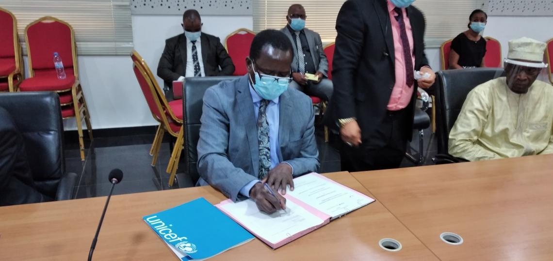 Dr Pierre Ngom, Représentant Résident de l'UNICEF en train de signer une convention avec le gouvernement guinéen pour soutenir l'éducation