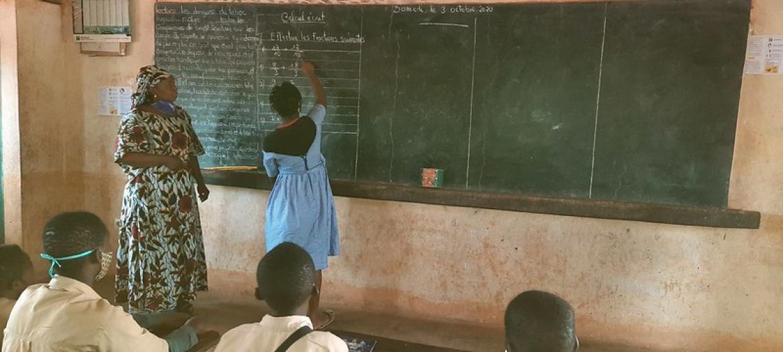 Cécile Kamano en train d'écrire au tableau sous la vigilance de son enseignante