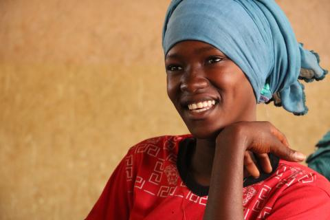 Smiley teenage girl with headwrap in classroom