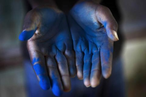 A man shows his hands after the mapping the boundary of the village made blue by paint powder.