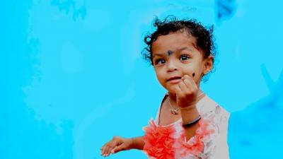 A girl child plays with a blue background behind her