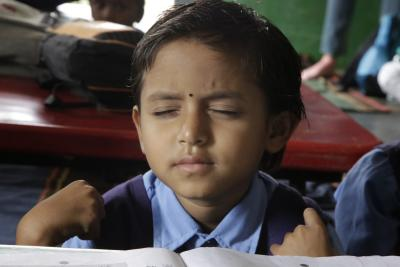 A child in school uniform sitting at a desk in class with their eyes shut thinking.