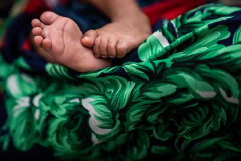 A newborn child rests on a cot after being examined by Kiran Devi, an Accredited Social Health Activist (ASHA) as part of Home Based New Born Care inside a hamlet in Shrawasti, Uttar Pradesh.