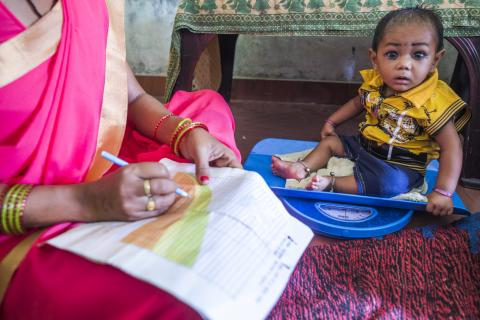 An Aanganwadi worker weighs a child on a digital scale as she records the details on a MCP card a during a meeting as part of Village Health and Nutrition Day (VHND) in Motipur Kala Aanganwadi Centre in Shrawasti, Uttar Pradesh.
