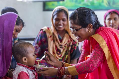 Rimpi Rani, an Aanganwadi worker feeds a child during a meeting as part of Village Health and Nutrition Day (VHND) in Motipur Kala Aanganwadi Centre in Shrawasti, Uttar Pradesh.