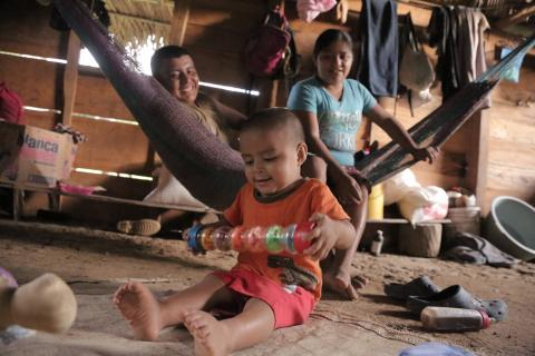 On 15 August 2016 in Belize, Abner Choc, 2, sitting on an old mat on the dirt floor, plays with a toy at home, in San Felipe Village in the Toledo region.
