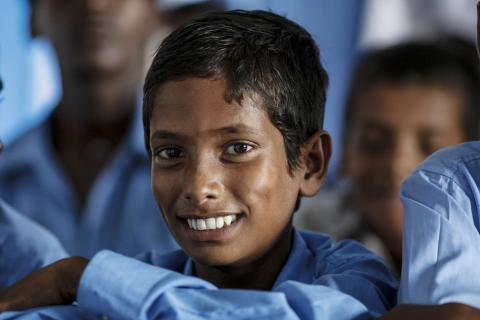 A student smiles during a meeting with School Disaster Management Group (SDMG) on School safety interventions at Middle School in Supaul District, Bihar.