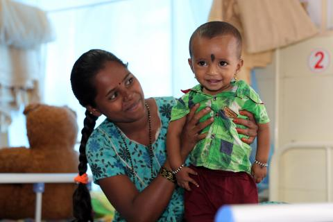 A Young happy mother looking at her son who has improved with handsome weightgain after getting treated for SAM in Chikkabalapur Nutrition Rehabilitation Centre (NRC) Karnataka.