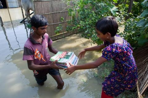 Children transporting books during floods in Bangladesh in 2019.