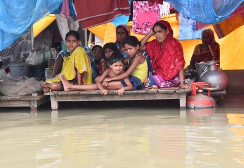A family sit in their house surrounded by water during floods in Assam.