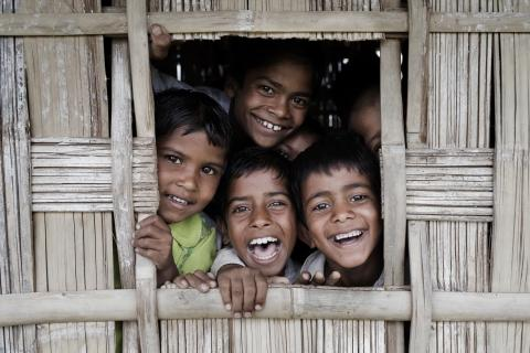 Indian children crowd at the window of a classroom at a Feeder School, in Lowkiwali Village, in Lahoal Block, on Mesaki Island, Dibrigarh District, Assam, India.