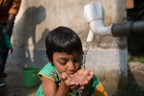 A girl cups her hands under a tap and drinks clean water