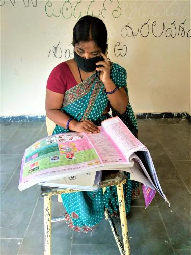 A community health worker on the phone and with a counselling guide book on her lap.