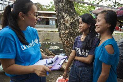 A UNICEF health worker interviewing two young girls.
