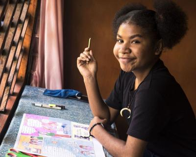 Melan, 14, draws a comic in her home in Sorong