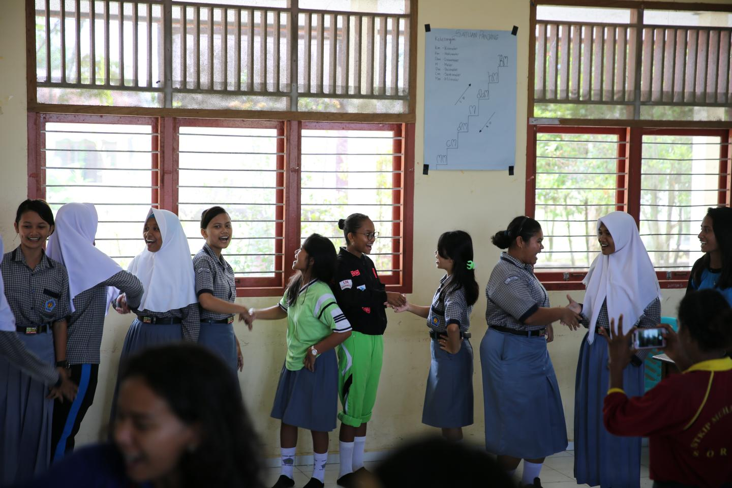 Adolescent Indonesian girls in a classroom taking part in games