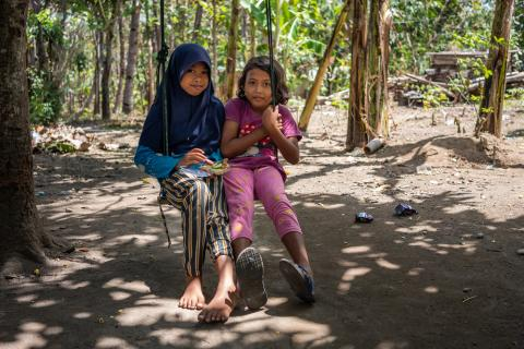 Two girls eat as they sit together on a swing outside their home in Central Java province, Indonesia.
