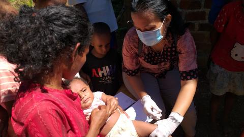 Health worker provides vaccinations to children