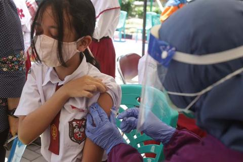 A worker vaccinates a student