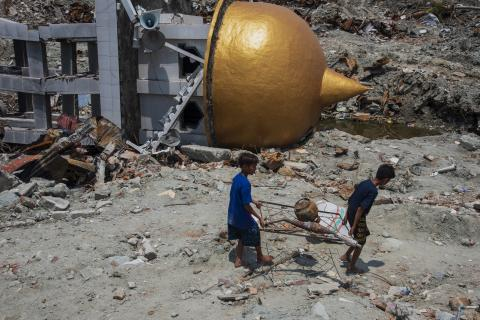 Boys and a fallen mosque after the earthquake in Sulawesi 2018