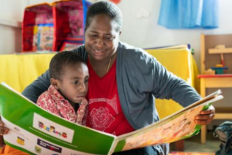 A mother reads to her daughter in a preschool.