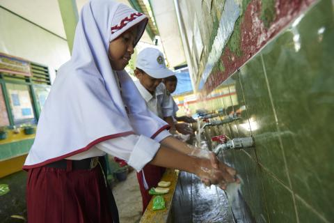 Children use soap to wash their hands at a primary school