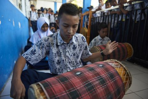A young boy playing an instrument in school.