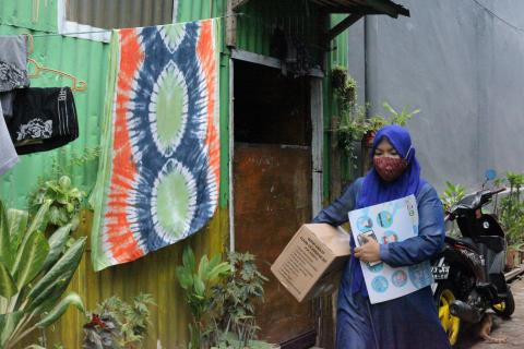 Biah, a health volunteer, visits residents in Makassar to educate them about COVID-19 and distribute hygiene kits.