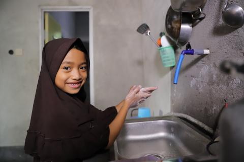Girl washing hands in her kitchen